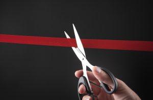 scissors cutting red tape
